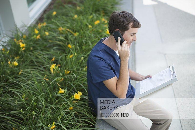 medical technician having telephone conversation outside