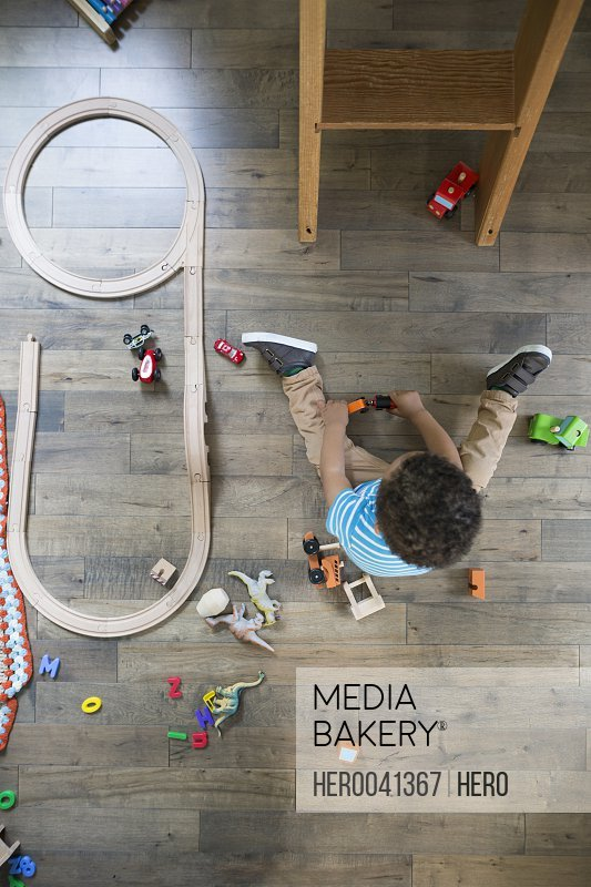 Overhead view boy playing with toy cars on hardwood floor