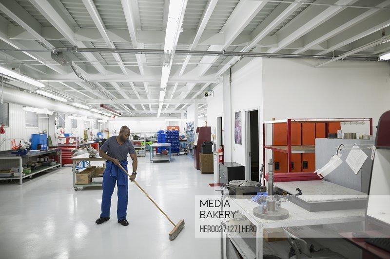 Helicopter mechanic sweeping workshop floor