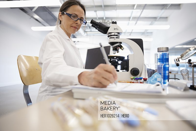 Female scientist working at microscope in laboratory