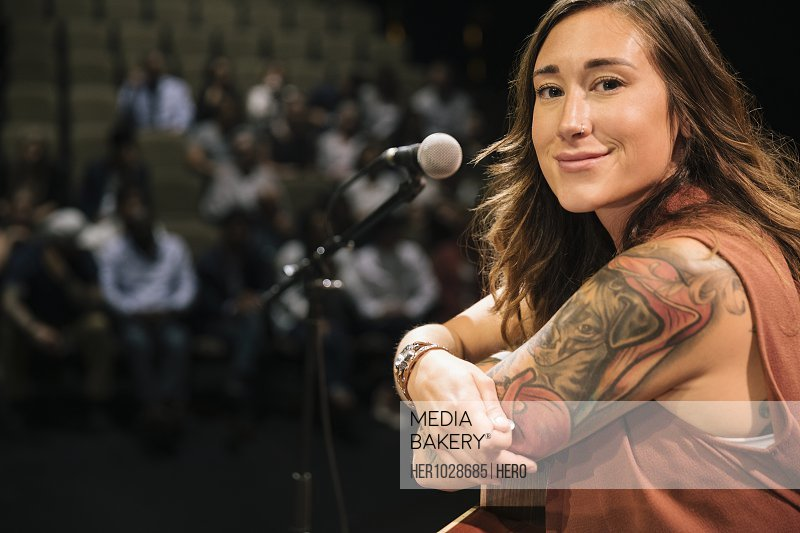 Portrait confident female musician with tattoos on stage