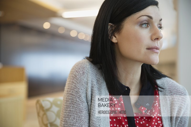 Mid adult businesswoman looking away in office