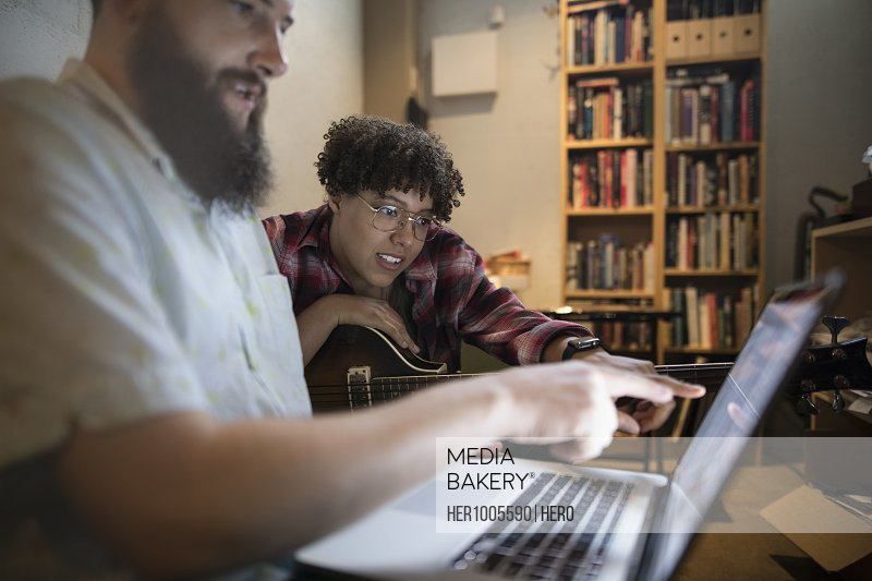 Musicians with guitar writing music at laptop