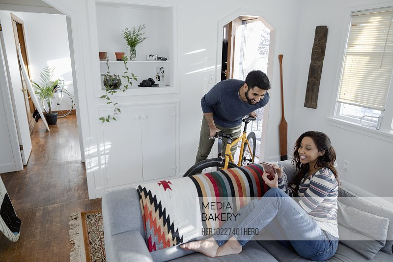 Couple with smart phone and bicycle in living room