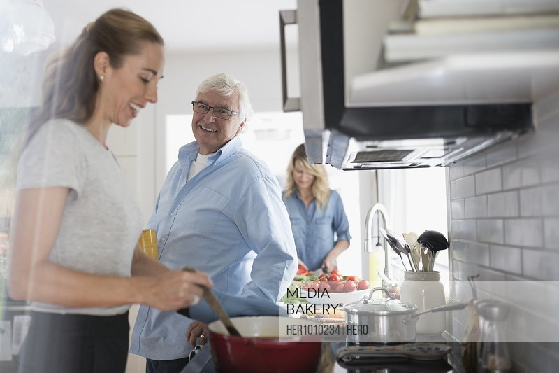 Smiling daughter and senior father cooking at stove in kitchen
