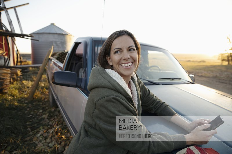 Smiling, happy female farmer using smart phone at pickup truck on farm