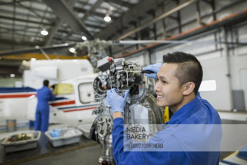 Smiling mechanic working on helicopter part airplane hangar