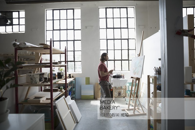 Male painter painting at canvas on easel in art studio