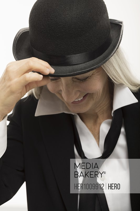 Confident, smiling senior woman wearing suit and hat