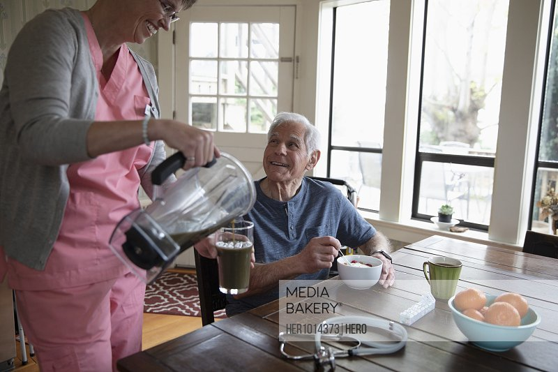 Home caregiver pouring green smoothie for senior man at kitchen table