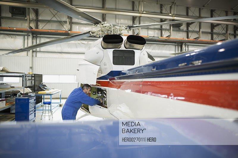 Helicopter mechanic repairing engine in airplane hangar