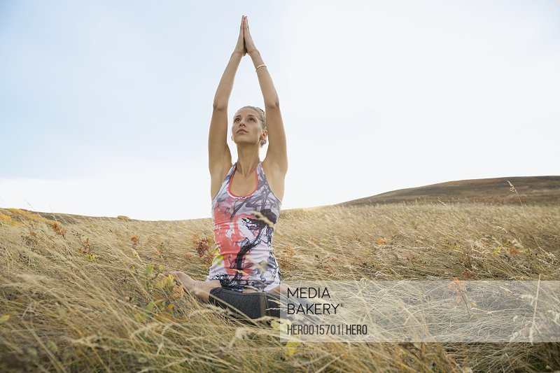 Serene woman practicing yoga in rural field