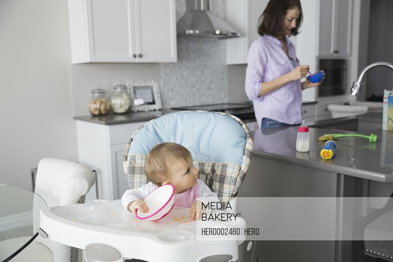 Cute baby girl with mother in kitchen