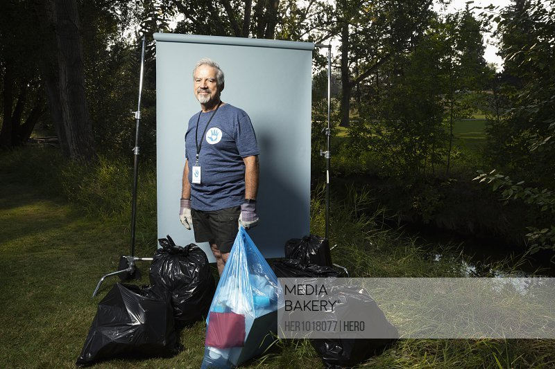 Portrait confident senior man volunteering, cleaning up garbage in park, posing against white screen