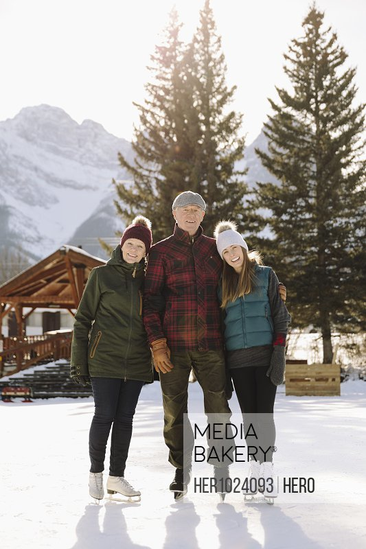 Portrait senior couple and daughter ice skating on frozen pond