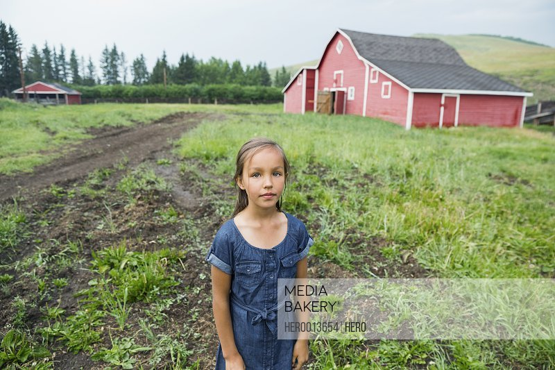 Portrait of girl in rural pasture outside barn