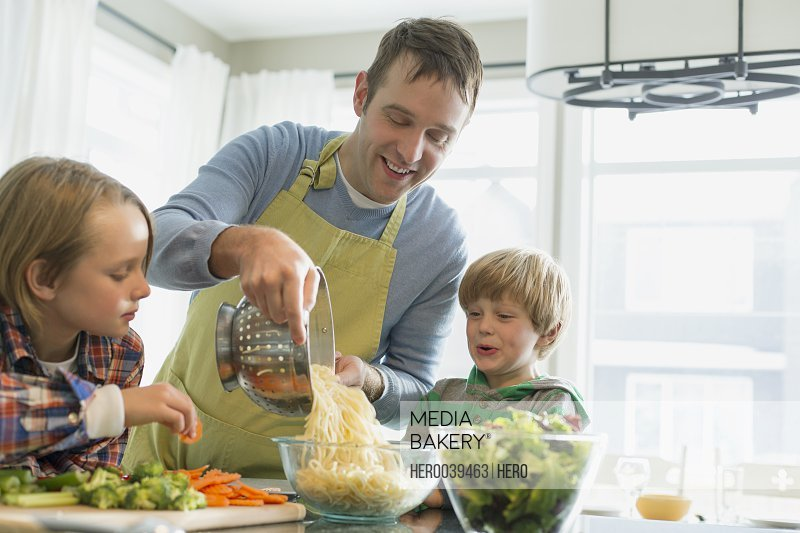 Father putting spaghetti into bowl as sons watch