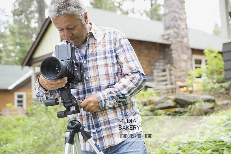 Middle-aged man adjusting lens of SLR camera in yard