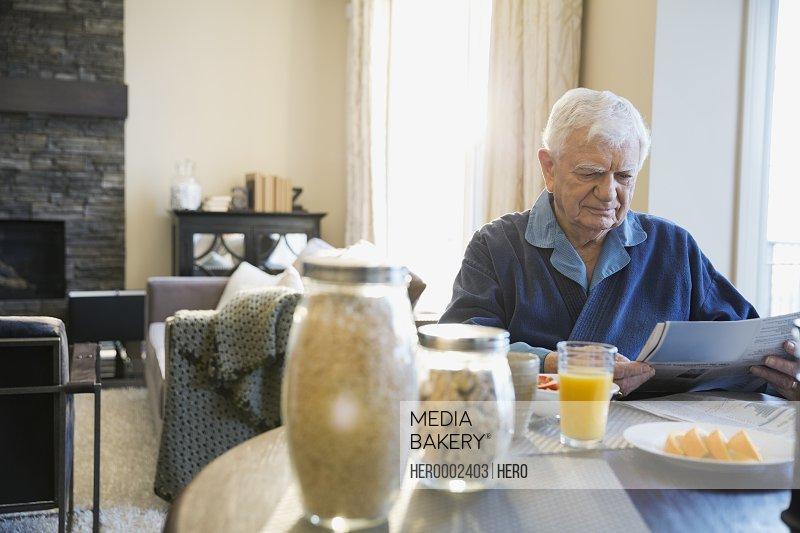Senior man reading newspaper at breakfast table