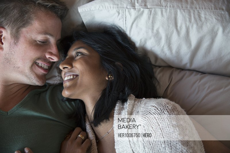 Overhead view smiling, affectionate couple laying in bed