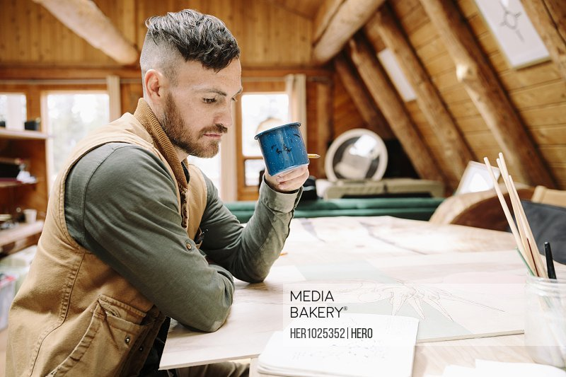 Male artist drinking coffee at cabin table