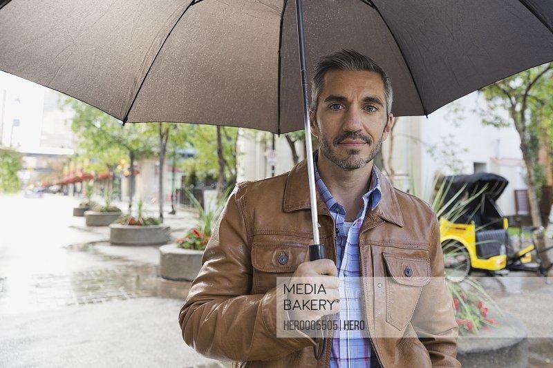 Portrait of man holding umbrella on city street