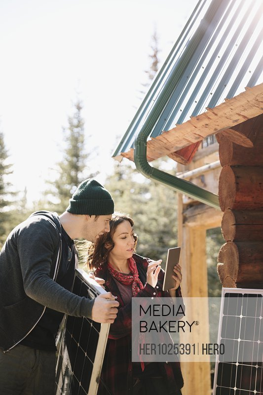 Couple with digital tablet installing solar panels outside cabin