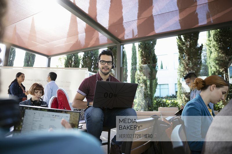 Male hacker using laptop during hackathon on patio