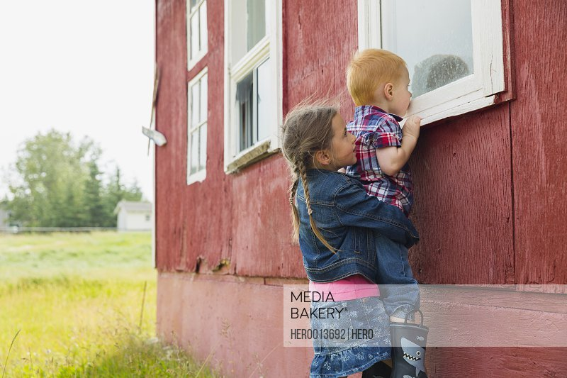 Sister lifting curious brother to look inside window