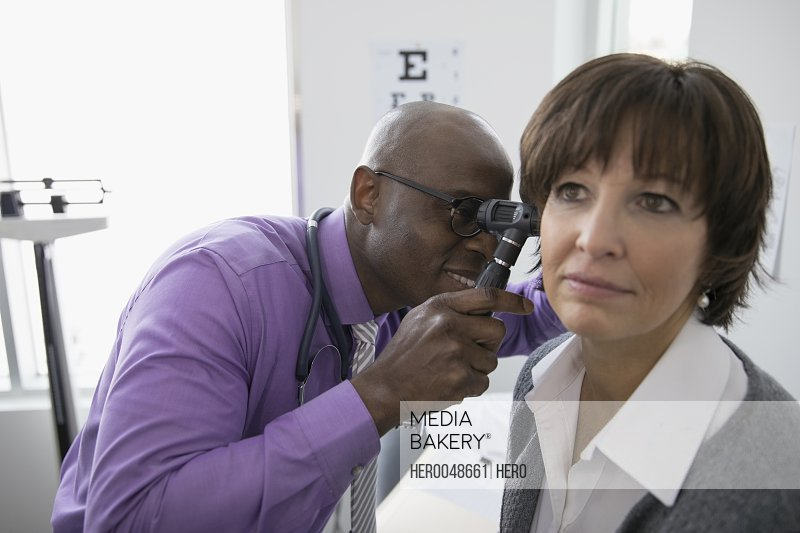 Male doctor examining ear of female patient with otoscope in medical examination room