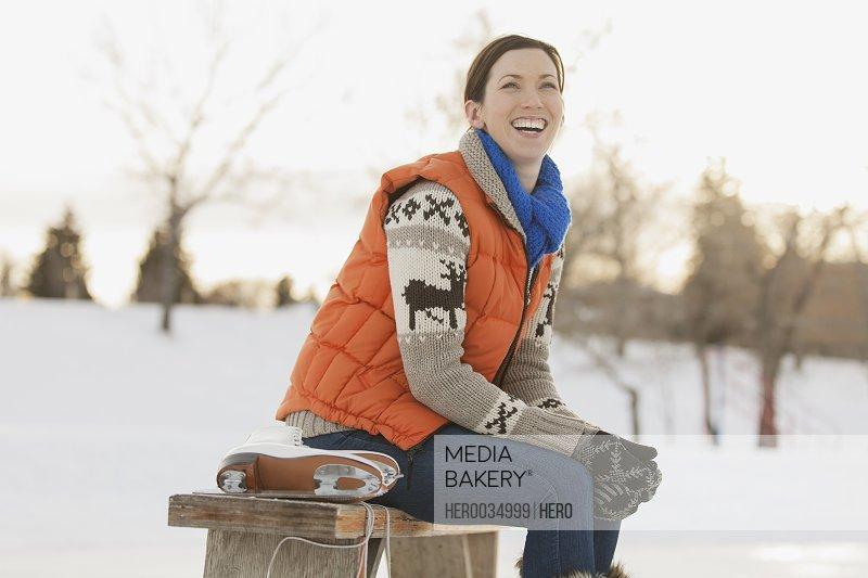 Cheerful woman putting on ice skates