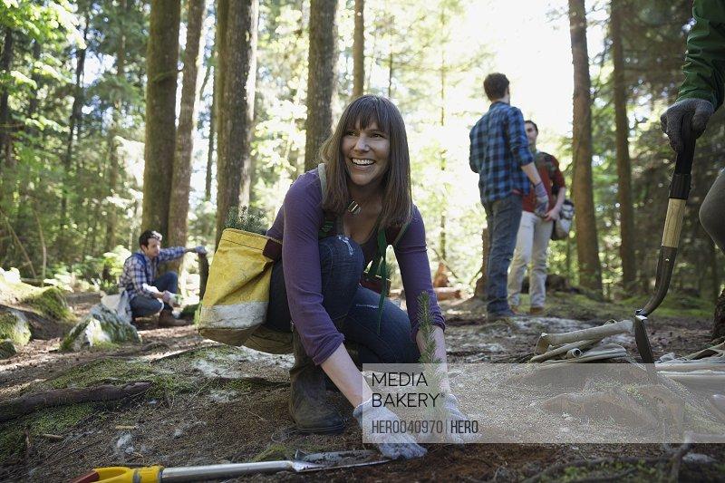 Smiling volunteer planting tree in woods