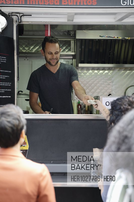 Food truck owner taking money from customer