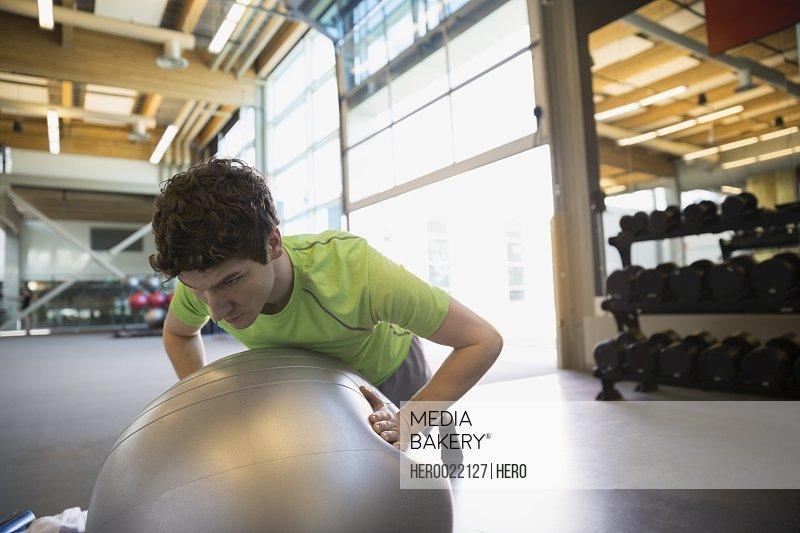 Man doing fitness ball push-ups at gym