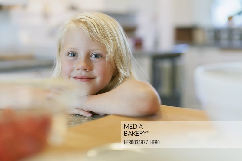 Cute young girl leaning on counter.