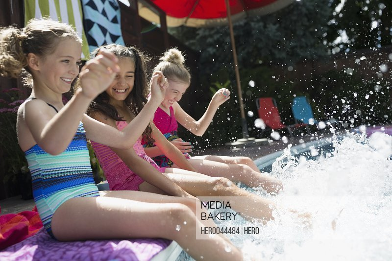 Playful girls at poolside splashing feet in water