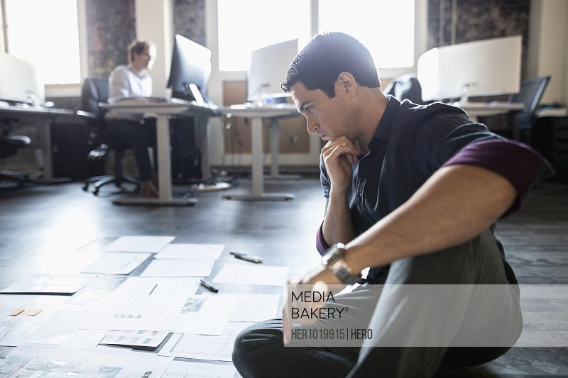 Focused creative businessman reviewing proofs on office floor