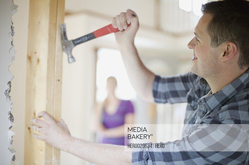 homeowner pulling nails from wall