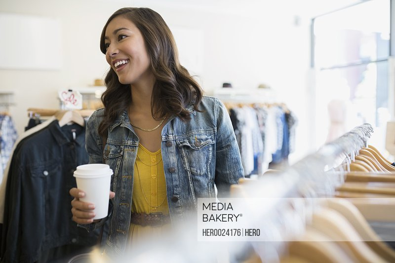 Woman with coffee in clothing shop