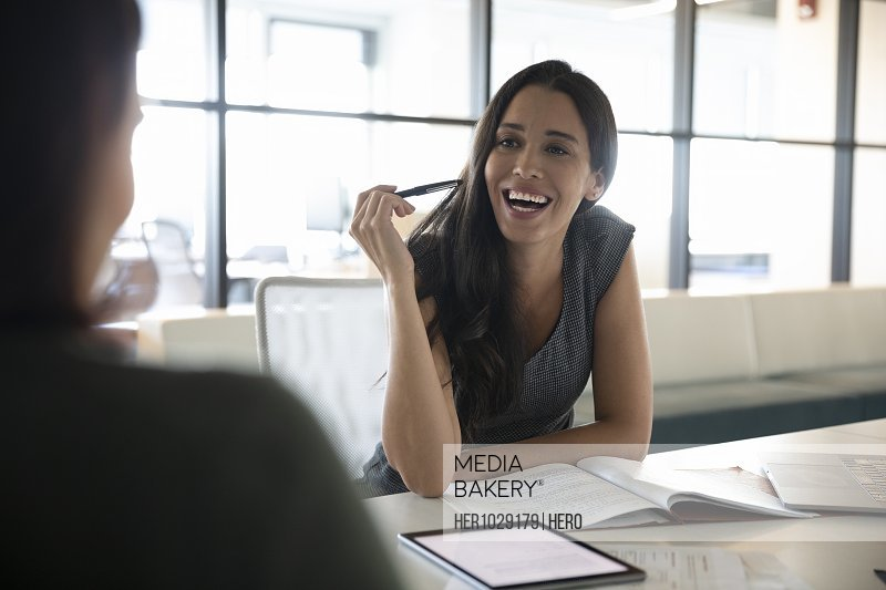 Businesswoman in meeting with colleague smiling