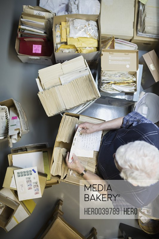 Overhead view of senior man reading old letters