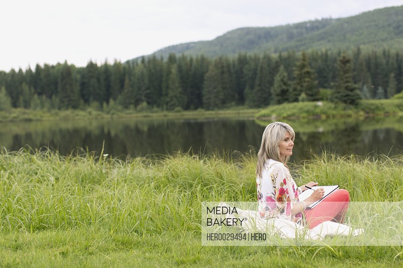 middle aged woman sketching in meadow by water