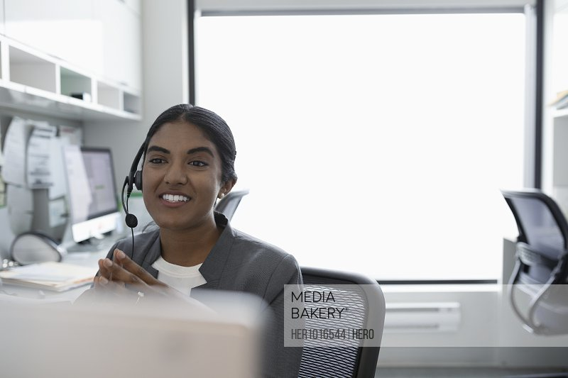 Smiling woman using hands-free telephone in clinic office