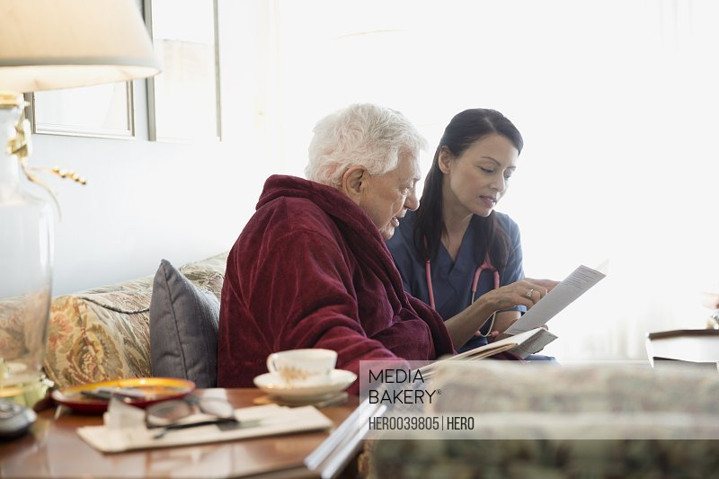 Home caregiver discussing pamphlet with senior man