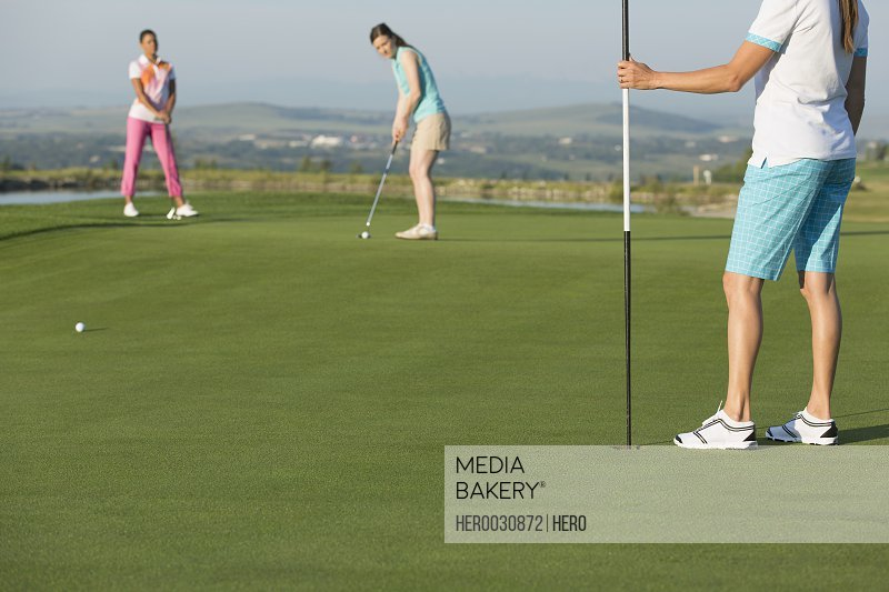 female golfer putting on golf green