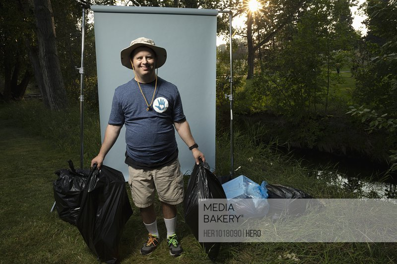 Portrait confident man with down syndrome volunteering, cleaning up garbage in park, posing against white screen