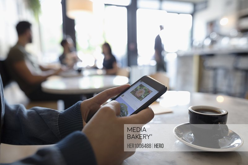 Close up woman using digital tablet and drinking espresso in cafe