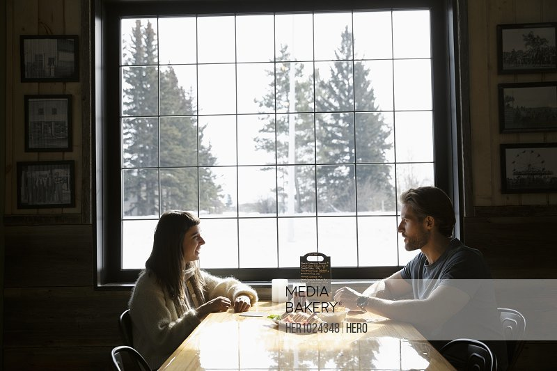 Couple enjoying lunch in brewhouse at snowy, winter window