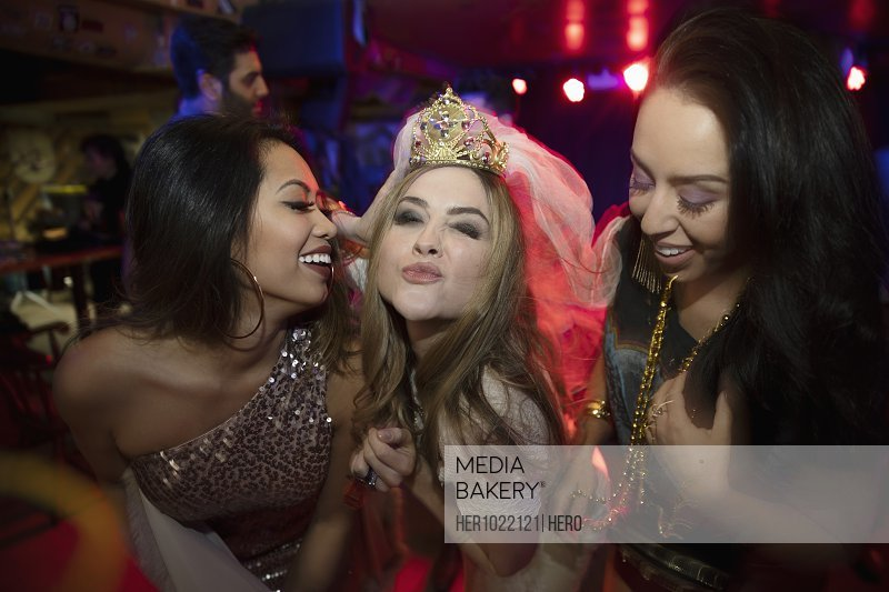 Portrait confident bachelorette with friends in nightclub
