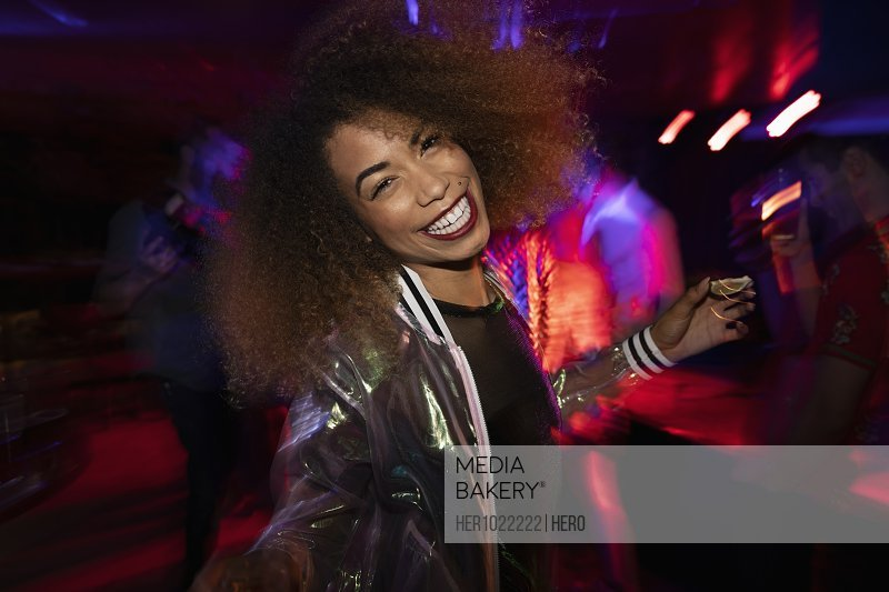 Portrait carefree young woman dancing in nightclub